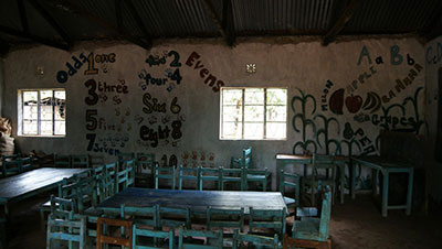 Children's Classroom With Tables And Chairs And Paintings On The Wall